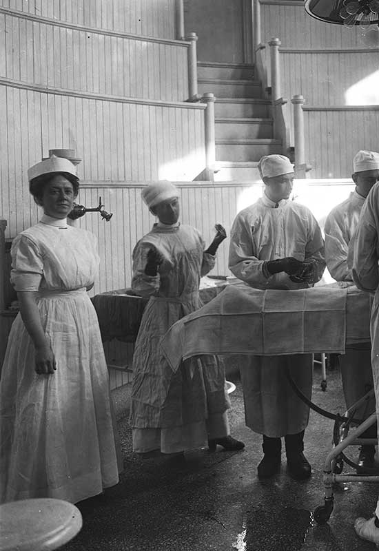 Operating room scene, 1913. To the far left is Tabitha Grier, RN, operating room nurse supervisor, who graduated from the U.Va. nursing program in 1912 and served as superintendent from 1913 to 1916.  Surgical Amphitheater, University of Virginia Hospital, 1913-02-08, Hollsinger Collection, Albert and Shirley Small Special Collections Library, University of Virginia