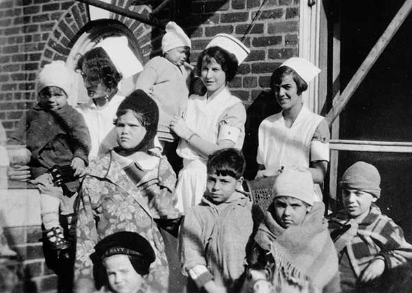 Student nurses and pediatric patients enjoy fresh air and sunshine on the roof of the hospital, c.1925.