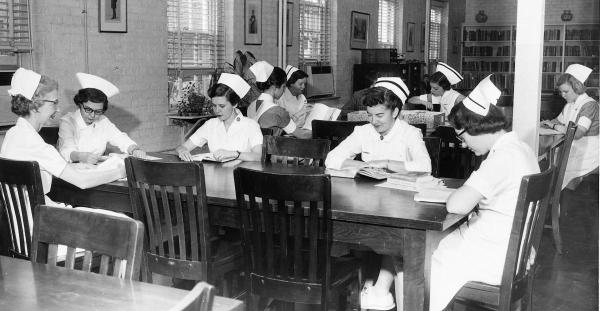 Faculty members and students at work in McKim Hall library, c. 1958.	Eleanor Crowder Bjoring Center for Nursing Historical Inquiry, University of Virginia School of Nursing. Ralph Thompson, Photographer.