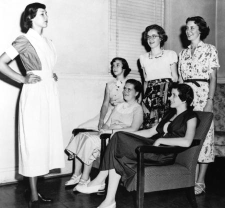 In 1950, Mary Washington College students look over the uniform they will be wearing as members of the school's first BSN class.	Uniform modeled by Frances Jones (later Schwark), BSN 1954. Eleanor Crowder Bjoring Center for Nursing Historical Inquiry, University of Virginia School of Nursing.