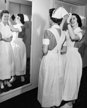 A 1954 second-year student admires the new black band on her cap, adjusted by a classmate.	Mildred Corum (later Campbell), BSN 1956, adjusts the cap of June Finlay (later Cain), BSN 1954. Eleanor Crowder Bjoring Center for Nursing Historical Inquiry, University of Virginia School of Nursing.