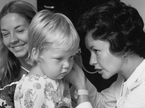 A pediatric nurse practitioner student performs a check-up.	Clinical instructor Beth Lawton & Barbie Dunn, MSN 1974 with pediatric patient. ECBCNHI Barbara Brodie Photograph Collection.